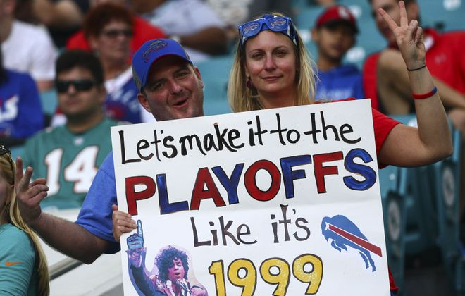 Fans at the Bills' Week 17 game at Miami hold a sign hoping for the team's first playoff berth since 1999. (James P. McCoy / Buffalo News)