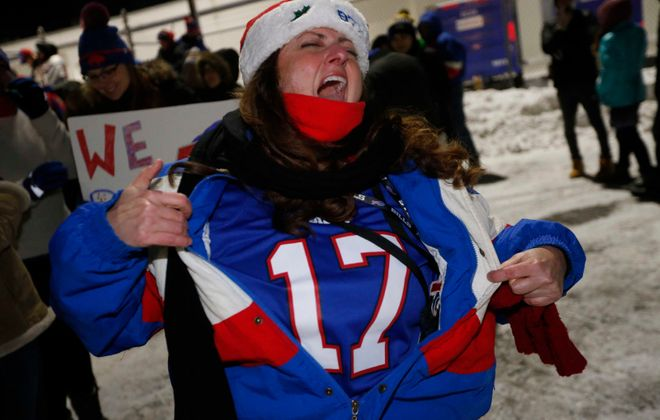 """A jubilant Mary Ellen Bossert of Hamburg opens up her jacket as she shouts """"Seventeen years!"""" while welcoming the Bills home at the airport Dec. 31. (Derek Gee/Buffalo News)"""
