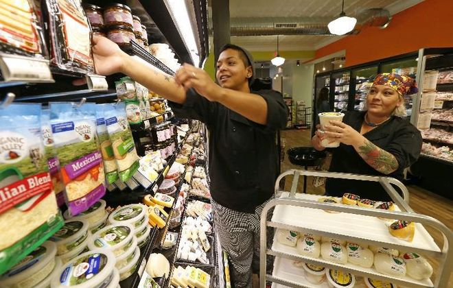 Workers stock cheese and dairy items at the East Aurora Co-Op, which opened in summer 2016. A group of volunteers wants to bring a similar cooperative market to Williamsville. The group is launching a membership drive at the village Farmer's Market.  (Buffalo News file photo)