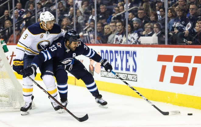 Evander Kane and Winnipeg defenseman Dustin Byfuglien battle for the puck during first-period action (USA Today Sports).