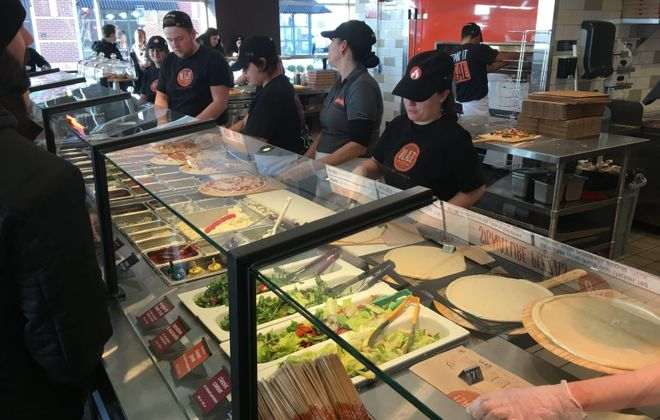 The walk-through order counter at Blaze Pizza is fully stocked with an array of ingredients to suit the pickiest pizza predilections. (Phil Wagner/Special to The News)