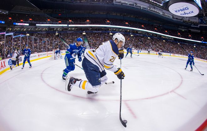 Sabres forward Kyle Okposo looks for open ice as Vancouver's Henrik Sedin gives chase Thursday night. (USA Today Sports)