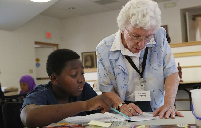 Sister Kathleen Dougherty works with Somali Bantu children in a West Side afterschool program, run by the Sisters of St. mary of Namur. (Sharon Cantillon/The Buffalo News)