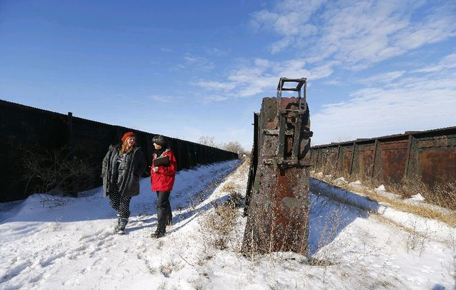 """Sara Heidinger, left, a First Ward coffee shop owner and Nancy Smith, executive director of the Western New York Land Conservancy, explore an old rail bed hoping to be revived as an elevated trailway in Buffalo, a kind of """"High Line"""" near South Park  Avenue. (Mark Mulville/The Buffalo News file photo)"""