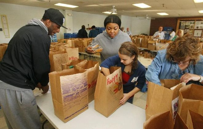 Volunteers at the City Mission bag food to help feed Buffalo's poor. A new Truth Commission wants to make politicians focus on poverty even as the new tax bill is likely to expand the gap between the haves and the have-nots. (John Hickey/News file photo)