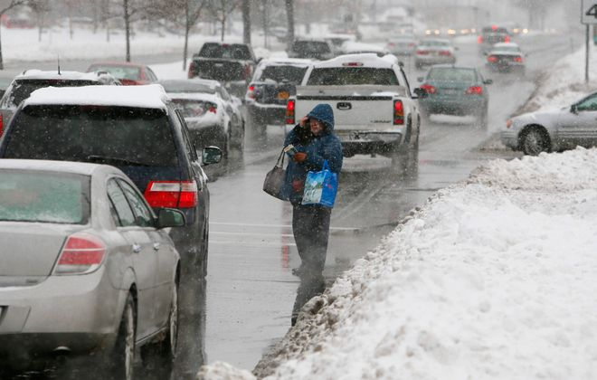 Beverly Schmitt of Buffalo stands in the middle of Niagara Falls Boulevard in Tonawanda while waiting for the bus because the snowbanks were three feet high. (Derek Gee/Buffalo News)