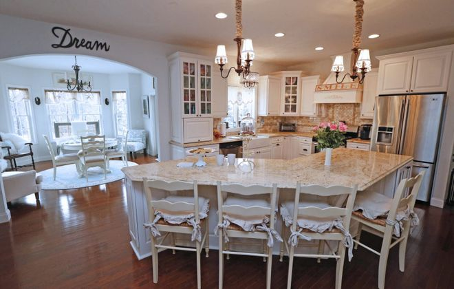 """The King family's kitchen features an island, granite countertops and off-white cabinets. The kitchen opens to the """"morning room."""" (Robert Kirkham/Buffalo News)"""