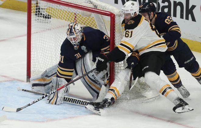 Sabres goaltender Chad Johnson gets the stick down as defenseman Victor Antipin chases Bruins forward Rick Nash. (James P. McCoy/Buffalo News)
