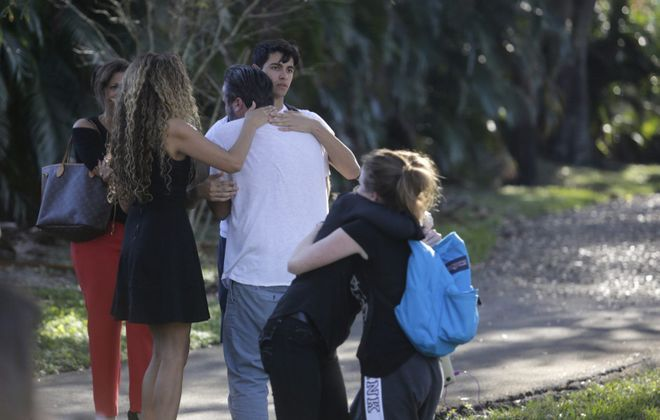 Parents and students gather outside the Marjory Stoneman Douglas High School during a shooting incident in Parkland, Fla., Feb. 14, 2018. (Saul Martinez/New York Times)