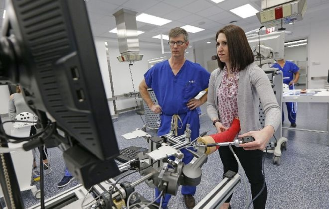 Dr. Stephanie Grilli, right, an orthopedic surgery sports medicine fellow at Jacobs School of Medicine and Biomedical Sciences, works on a simulator in the medical school's new Surgical Skills Simulation Center, as Dr. John Marzo, one of her mentors and center directors, looks on. Grilli is helping tend to the medical needs of  Buffalo Bills players through July. (Robert Kirkham/Buffalo News)