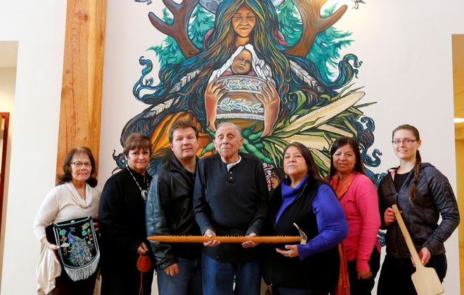 """Members of the History group of the Tuscarora Nation, are, from left, Judy Judware, Yehsenaruhcreh Wendy Bissell, Vince Schiffert, Chief Leo Henry, Gagehatdat Schandream, Angela Jonathan, and Taylor Hummel, stand in front a a mural at the Tuscarora Nation House. The group will host a """"Rez Life"""" event March 17. (Mark Mulville/Buffalo News)"""