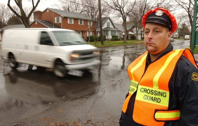 Crossing guard Mike Koenig stands watch at the corner of Payne Avenue and Walck Road in North Tonawanda in March 2013. The city plans to change the traffic pattern on Payne Avenue from Walck Road to Meadow Drive. (Buffalo News file photo)