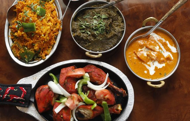 Clockwise from top left, the vegetable biryani, saag paneer, chicken makhani and the tandoori chicken at Tandoori Hut. (Derek Gee/Buffalo News)