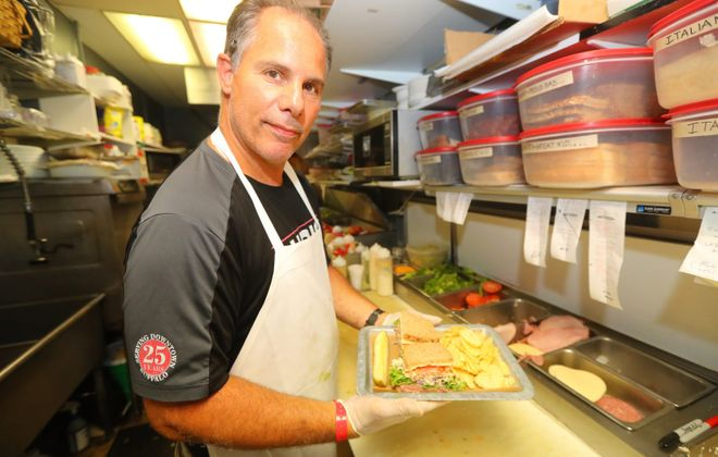 Chris Vendetti, owner of Chris's Sandwich Shop,  makes a Roast Beef Slawich. (John Hickey/Buffalo News)