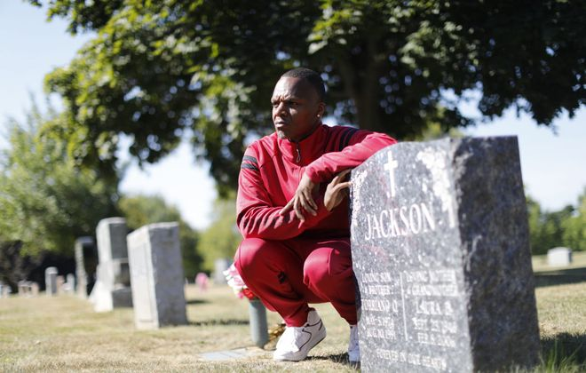 Aaron Jackson visits the grave site of his younger brother, Torriano Jackson, who was murdered by gunfire in 1991. (Derek Gee/Buffalo News)