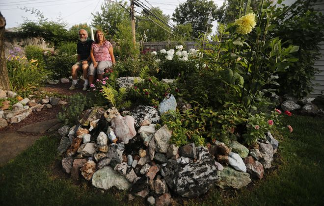 Dick and Jeanne Phillips take a seat in the backyard of their Town of Tonawanda home. They have thousands of collected rocks on their property. (Mark Mulville/Buffalo News)
