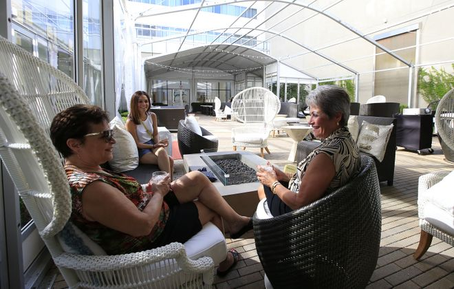 Mary Santiago, right, and her sister Eva, center, along with her daughter Celinda enjoy drinks at the Patina 250 Courtyard. (Harry Scull Jr./ Buffalo News)