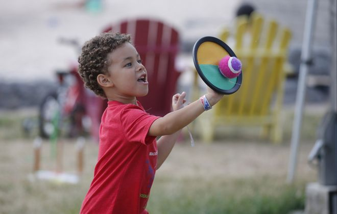 "Isaiah Winiarski, 5, of Buffalo catches a fuzzy ball with a hook and loop material disc at a  Sow Fit Buffalo Kids Get Moving fitness night alongside the ""beach"" at Canalside. Kids Get Moving starts at 6 p.m. Mondays and Fridays through August, except Aug. 3 and 17. (Robert Kirkham/Buffalo News)"