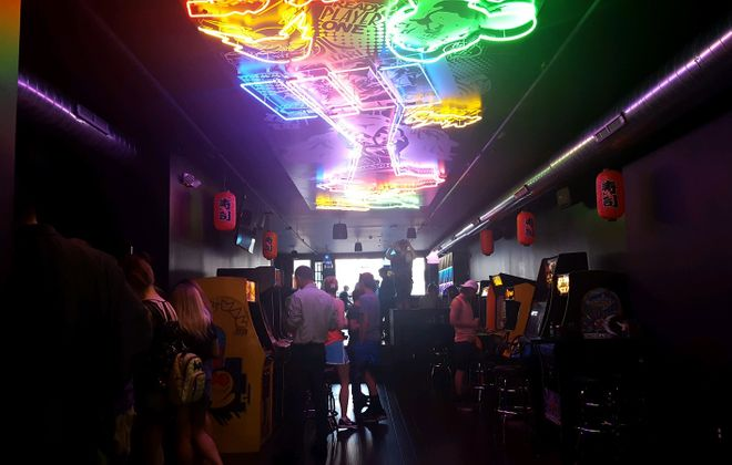Colorful fluorescent lights create the scene inside Misuta Chow's, a new arcade-restaurant-bar on Main Street. (Aaron Besecker/Buffalo News)