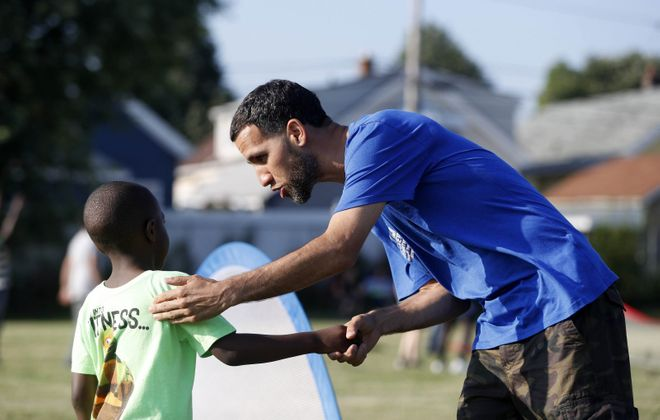 Teddy Rivera, a veteran of combat in Iraq, interacts with children during a pickup game at year-end party for the children's soccer club at Roosevelt Park in Buffalo. (Mark Mulville/Buffalo News)