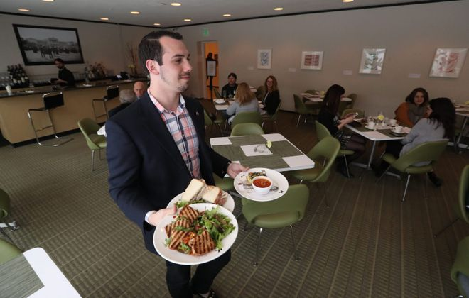 Assistant Manager Cory Wolin serves lunch to a table at the AK Cafe inside the Albright-Knox Art Gallery. (Sharon Cantillon/Buffalo News)
