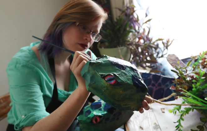 Artist Jessica Widmer makes a mutated two-headed sea turtle that will hang in Grindhaus Cafe on Allen Street as part of the Green Window City Project going on in May in Allentown. (Sharon Cantillon/Buffalo News)