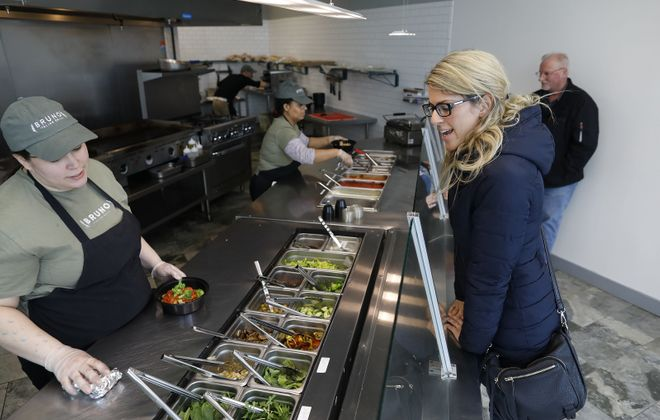 Melissa Lis builds a pasta bowl for customer Cassie Zbytek of Cheektowaga at Bruno Italian Grill. (Derek Gee/Buffalo News)