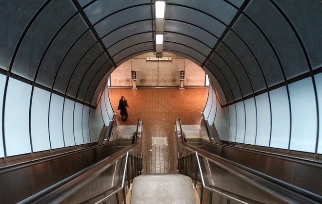 A woman takes the escalator in the tunnel underground at the Delevan/College NFTA Metro Rail subway station. (Derek Gee/News file photo)