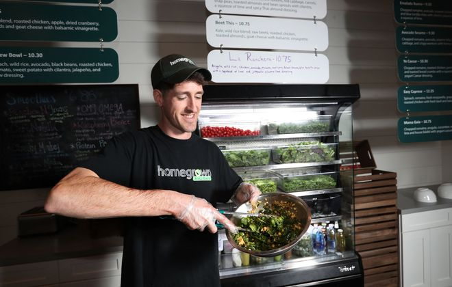 Owner Sean Lane mixes the Curried Away at Homegrown Kitchen in East Aurora after combining ingredients that include kale, spinach, wild rice, chickpeas, roasted chicken, red onion and raw corn and a spicy carrot curry dressing.  The dish falls into the guidelines of the Independent Health Foundation's Healthy Options program. (Sharon Cantillon/Buffalo News)