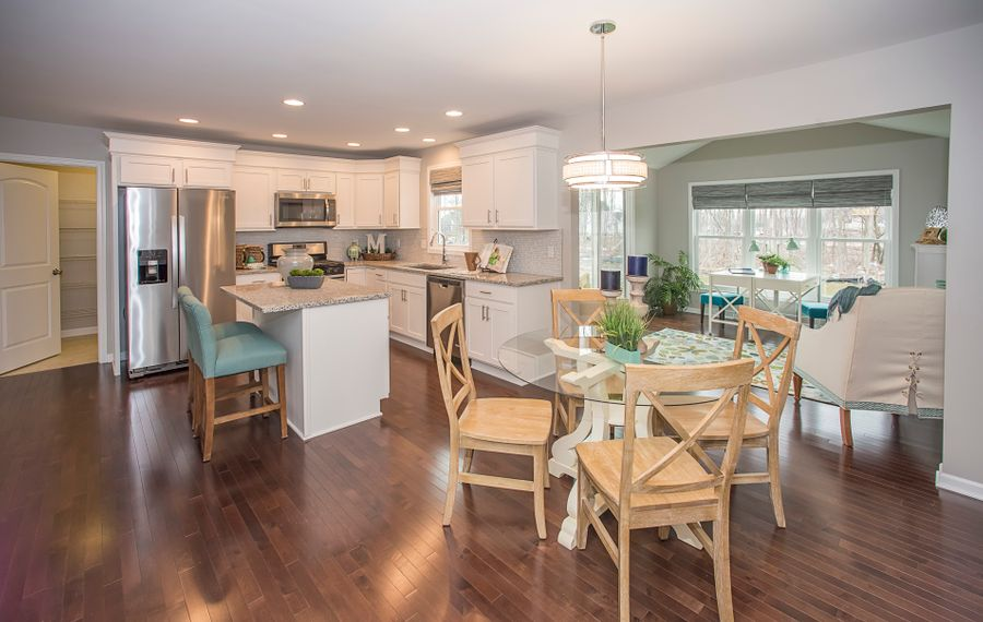 An open floor concept with a kitchen, dinette area and sunroom.