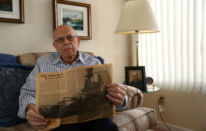Navy veteran Frank G. Buzzelli holds one of several newspapers he saved with images of the 1946 atomic bomb test he witnessed at Bikini Atoll. (John Hickey/Buffalo News)