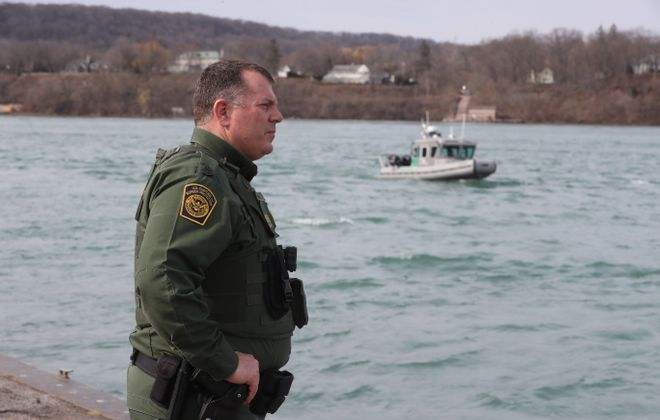Supervisory Border Patrol Agent Kevin Radke at Lewiston Landing on  Tuesday, April 24, 2018 with a border patrol boat in the background. (John Hickey/Buffalo News)