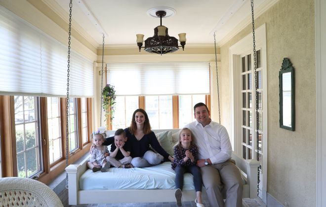 Theresa and Adam Roma with Maria, far left, and twins Louis and Estelle on the sun porch bed swing. (Sharon Cantillon/Buffalo News)