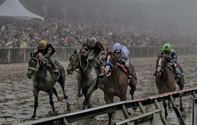 Justify splashes across the Preakness finish line. Photo Credit: Jon Kral/Maryland Jockey Club