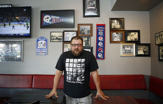 Naked City Pizza co-owner Chris Palmeri stands near a Buffalo-themed wall at Naked City Pizza on May 29 in Las Vegas. (Ronda Churchil/Special to The News)