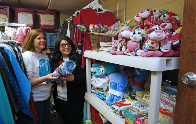 Foster mom Nanette Pohle, left, and Sarah Falzone, foster care intake coordinator with Gateway Longview, sort through donations in the agency's Clothing Closet, which accepts stuffed animals, jackets, onesies, blankets, pacifiers, diapers, car seats and more. The greatest need the agency has is a larger supply of foster parents. (Robert Kirkham/Buffalo News)