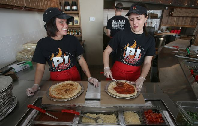 Pi Craft employees prepare pizzas at the restaurant when it opened in 2014. It has grown to include a food truck. (News file photo)