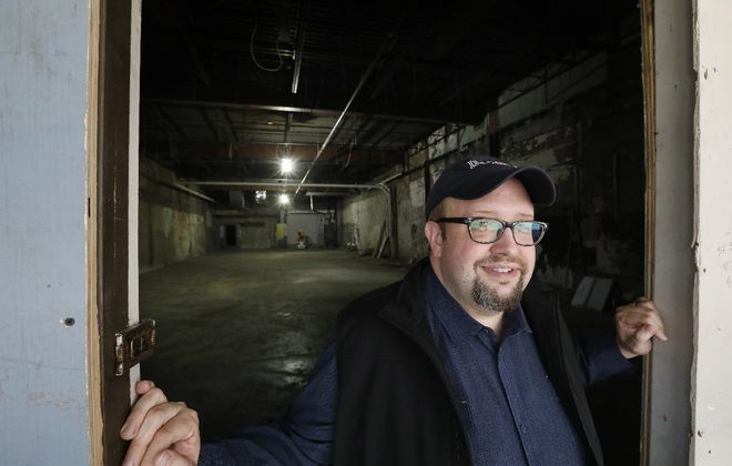 Scott Behrend, co-founder of Road Less Traveled Theatre, takes in the former Baker Shoe company space on Main Street where Road Less Traveled will build a new theater space to call home. (Derek Gee/Buffalo News)
