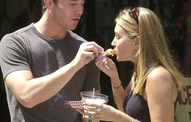 Nicole Glab, right, of Syracuse gets a taste of  bacon wrapped shrimp from fiance Jeff Glor, formerly of Buffalo, at Taste of Buffalo. (Robert Kirkham/News file photo)