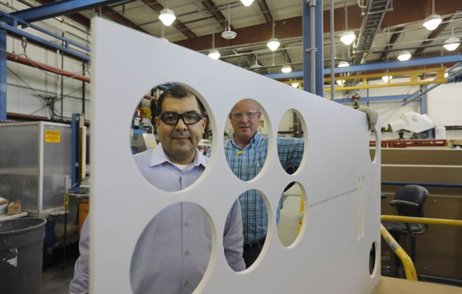 David Ledesma, (left) plant manager at DuPont Yerkes, and technology associate Christopher Karwas are framed by cuts in a sheet of Corian in the Applications Technology Center. (Derek Gee/Buffalo News)
