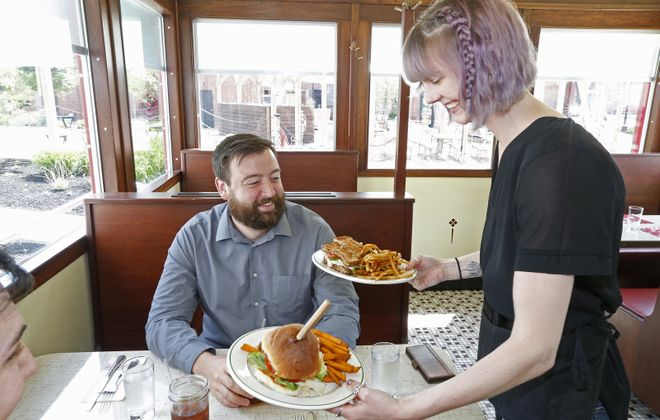 Swan Street Diner server Christie O'Brien delivers lunch to the booth of Derek Accurso. (Robert Kirkham/Buffalo News)