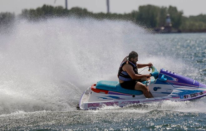 Abe Shafie of Buffalo cools off with the spray of his jet ski while riding in the Outer Harbor near Gallagher Beach on May 30. (Derek Gee/News file photo)