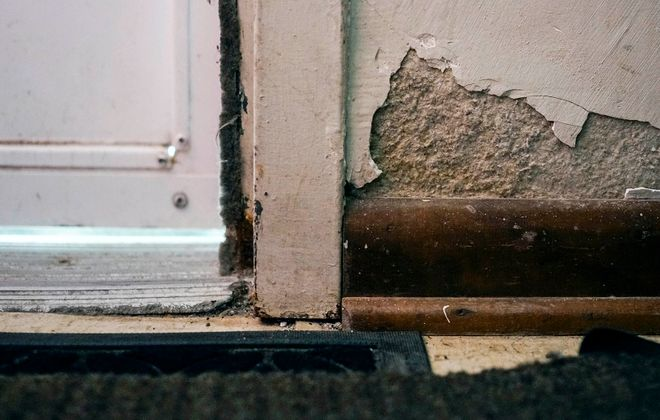Chipped plaster on the wall of an apartment in Langfield Homes in Buffalo. (Derek Gee/Buffalo News)