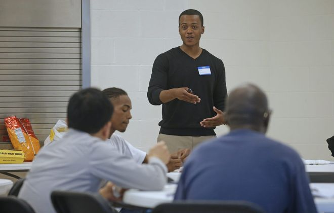 """Coordinator Antoine Johnson leads a discussion on """"teachable moments"""" the men experienced over the past week during a Nurturing Fathers Program session in the Delavan-Grider Community Center. (Robert Kirkham/Buffalo News)"""