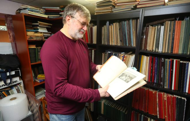 """William Greco, a former Roswell researcher, looks at a photo of Robert E. Schmidt as a freshman in a 1930 yearbook from Fosdick Masten High School in Buffalo. Schmidt went on to become the famed """"Buffalo Bob"""" Smith. Greco has almost 700 yearbooks, most from Buffalo, in his collection. (John Hickey/Buffalo News)"""