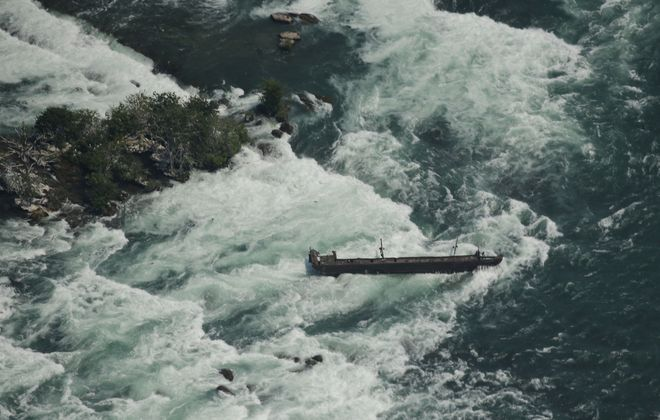 The scow, shown here in June 2018, was the site of one of the most dramatic rescues in Niagara Falls history. It  still rests on rocks in the rapids above the Horseshoe Falls in Niagara Falls, Ont. (Derek Gee/Buffalo News)
