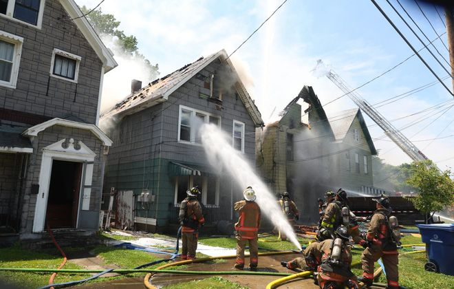 Buffalo firefighters battle a two-alarm blaze that spread to two adjoining homes on 700 block of Perry Street in Buffalo, N.Y., on Thursday, June 21, 2018. (John Hickey/Buffalo News)