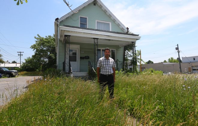 City Councilman Richard Fontana sometimes cuts the grass at 1277 Bailey Ave., which is owned by an out-of-town family. (John Hickey/Buffalo News)