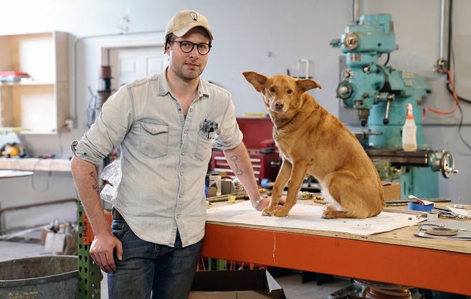 Andrew Emerson, the sole mind behind Emerson James Inc., in his workshop with his shop dog Igby. (Dave Jarosz)