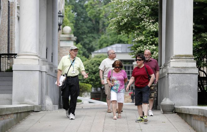 Harry Meyer, left, leads an Explore Buffalo tour of the mansions along Delaware Avenue in Buffalo on June 18. On the tour are, from left, David Stier, Helen Pilger, Sheila Price and Jim Bardot. They are leaving the former Butler mansion after walking its grounds. (Mark Mulville/Buffalo News)